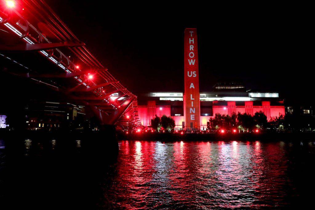 """La Tate Modern è illuminata di rosso mentre i sostenitori brillano anche di luci rosse dal Millennium Bridge come parte della campagna """"Throw Us a Line"""" di #WeMakeEvents che sostiene l'11 agosto 2020 a Londra, Inghilterra. Foto di Chris Jackson Getty Images"""